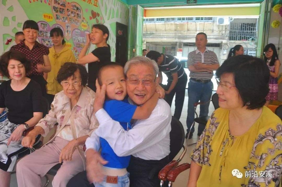 施金城与夫人梁丽馨在培文幼儿园,被幼儿园孩子抱住.png