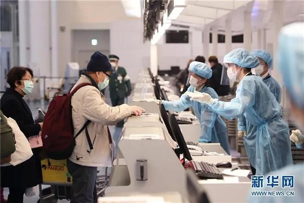 """2月20日,在日本东京羽田机场,""""钻石公主""""号邮轮的中国乘客(左)在柜台托运行李。 新华社记者 杜潇逸 摄.jpg"""